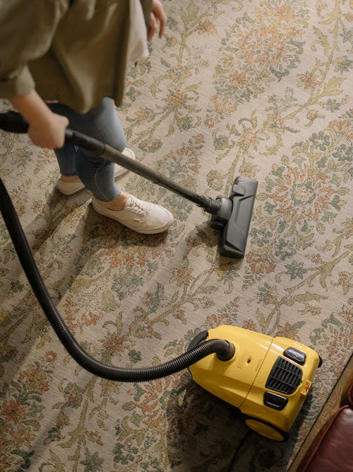 a person doing vacuum over a carpet