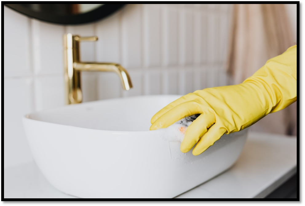 A gloved hand cleaning the bathroom sink