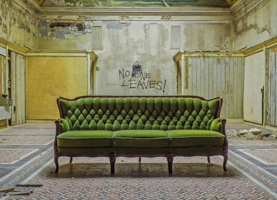 a room with a green couch and walls infested with mold