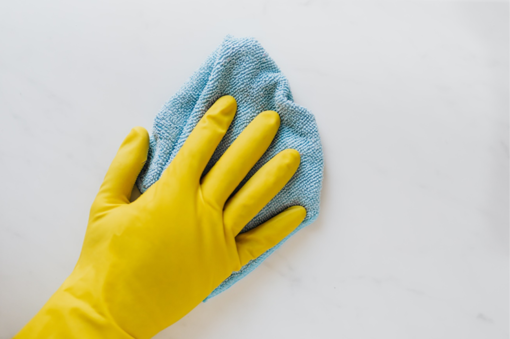 A professional cleaner wiping the kitchen wall wearing a rubber glove