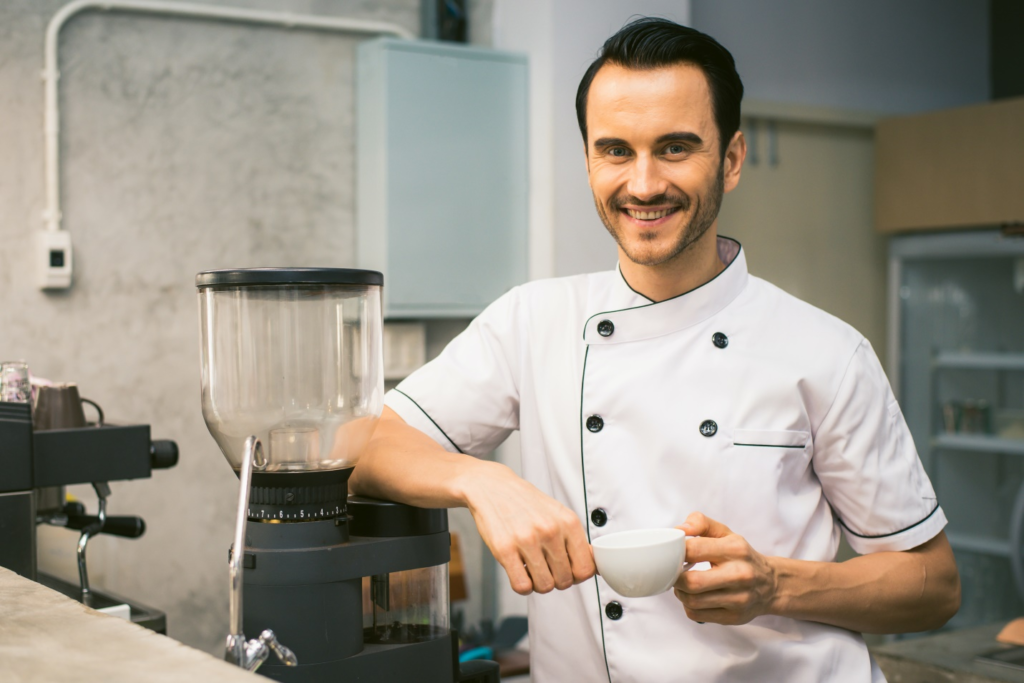 Chef standing in the kitchen smiling at the camera